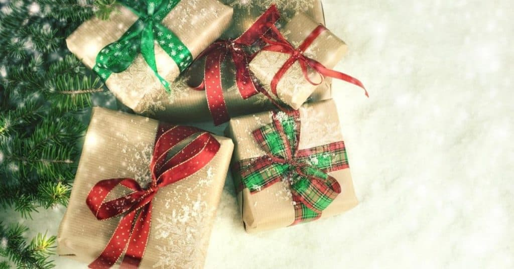 Presents wrapped in kraft wrapping paper and red and green ribbon - Best Christmas gifts for couples