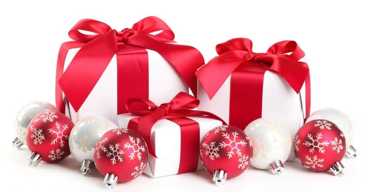 White presents with red ribbon and baubles - Best Christmas gifts for couples who have everything