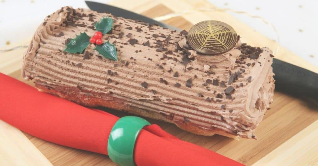 Yule Log Cake Decorated with Chocolate and Holly - Open for Christmas
