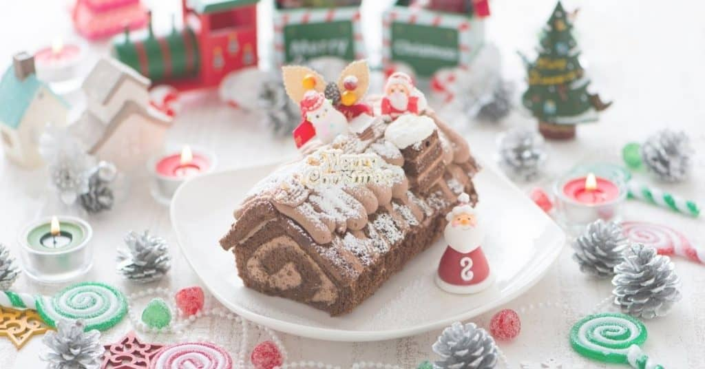 Yule Log Cake Decorated with Santa, snowman and other festive decorations - Open for Christmas