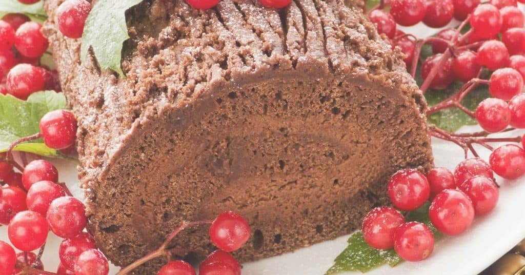 Yule Log Cake Decorated with festive berries and holly - Open for Christmas