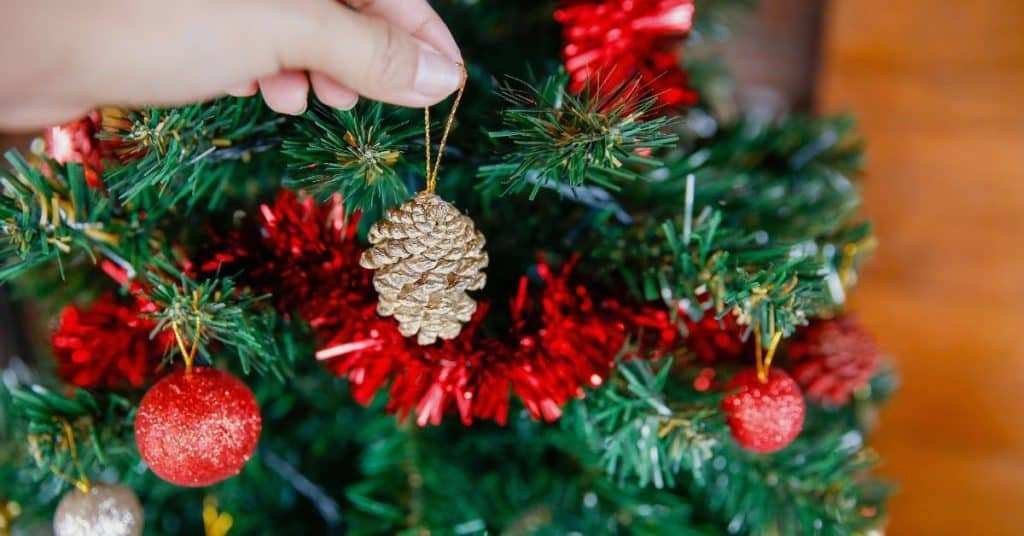 Red Tinsel and Baubles on a Christmas Tree - How to Decorate and Put Tinsel On a Christmas Tree - Open for Christmas