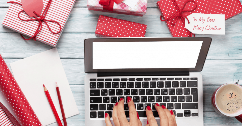 Laptop with lots Christmas gifts around - What To Buy Your Boss for Christmas - Open for Christmas