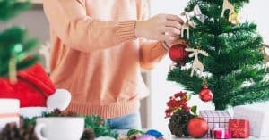 Woman Decorating the Best Small Mini Christmas Tree With Lights and Decorations - Open for Christmas